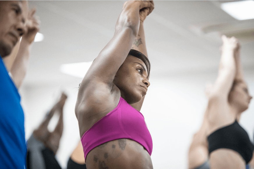 A woman taking part in a yoga class at Sweat Studios